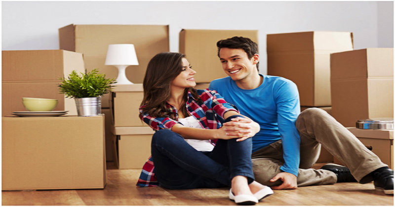 happy couple sitting on floor with cardboard boxes behind them