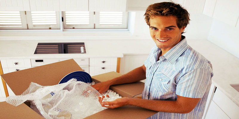 smiling couple holding packing boxes in hands