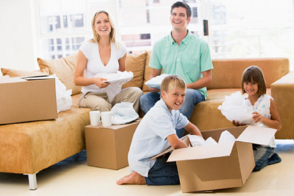 happy couple sitting on couch and packing their belongings while children pack sitting on floor