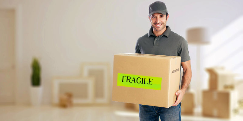 happy man in uniform carrying packed box with fragile items in hand