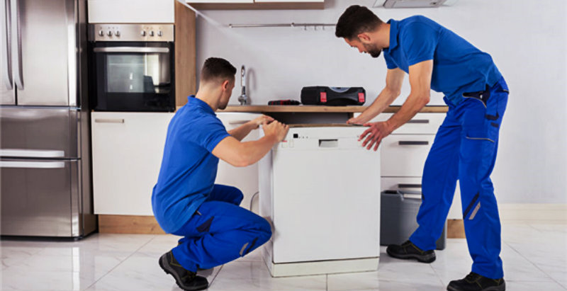 two mwn in blue uniform trying to lift a large kitchen appliance