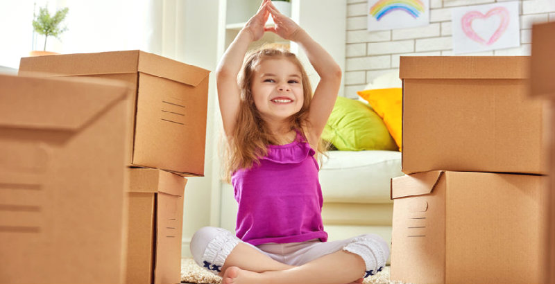 happy kid sitting in front of packed boxes