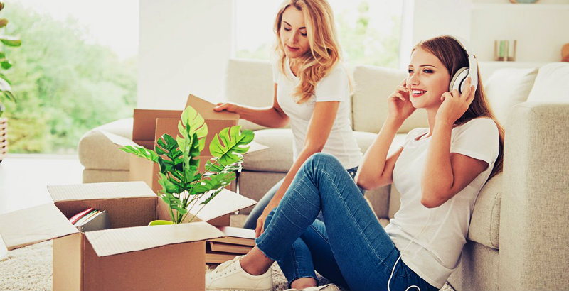 two beautiful young girls packing their belongings in boxes
