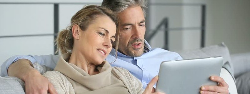 A couple is searching for something on a tablet