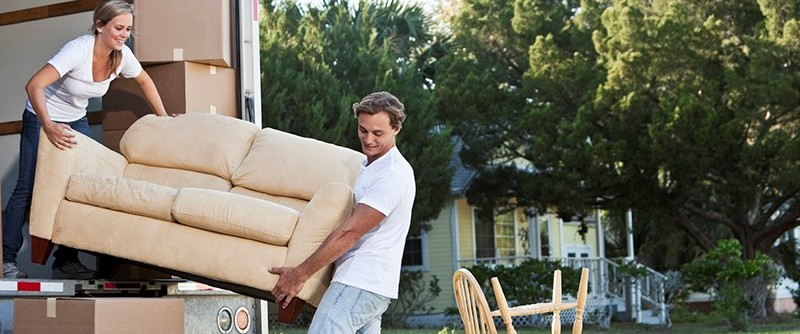 A couple is loading furniture in a truck