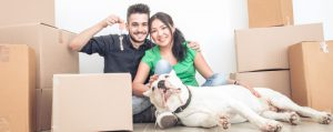 a couple sitting on the floor with a dog and some cardboard boxes