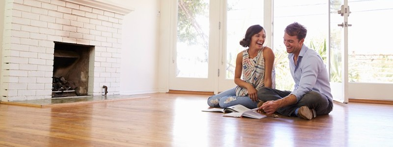 a couple sitting on the floor and planning to buy a property in Melbourne