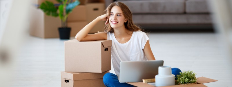 young woman sitting on the floor with her laptop and cardboard boxes
