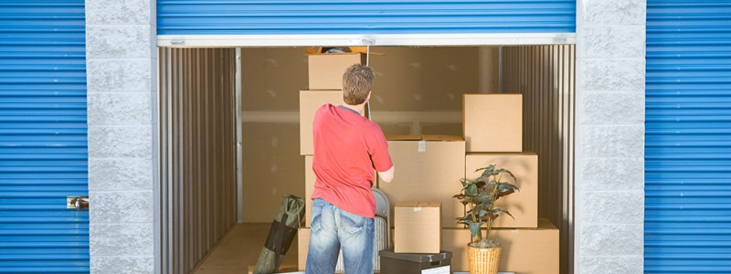 young man trying to close a storage unit