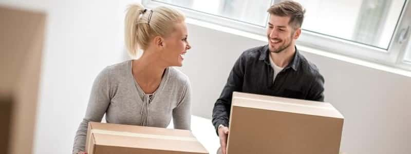 couple holding cardboard boxes vacating from a rental