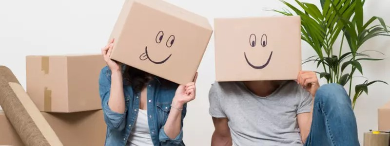 young couple covering their heads with cardboard boxes